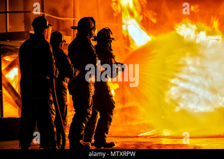JOHANNESBURG, SOUTH AFRICA - MAY, 2018 Firefighters spraying down fire during firefighting training exercise - Stock Photo