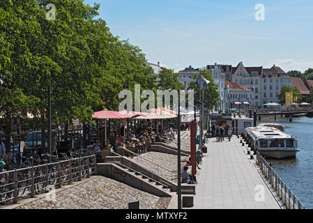 cafes with tourists on the bank of the trave river in the old town of lubeck, germany - Stock Photo