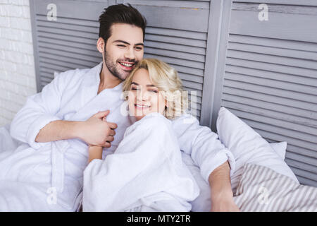happy young couple in bathrobes holding hands and lying together in bed - Stock Photo