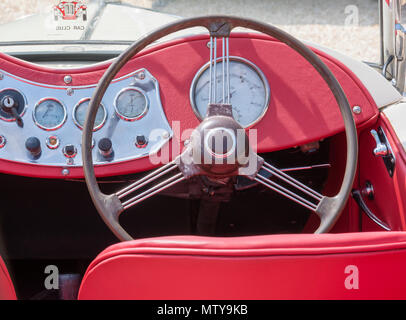 the steering wheel and dashboard of a vintage MG sports car with red leather upholstery and a wooden and metal steering wheel. vintage car interiors. - Stock Photo