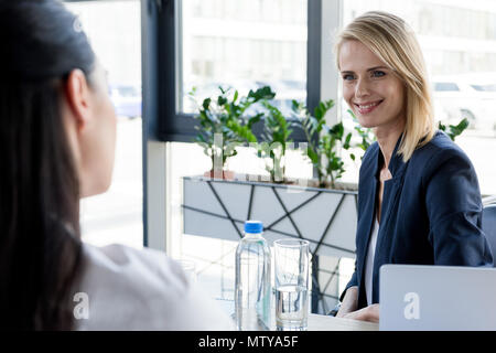 cropped shot of businesswomen talking and looking at each other in office - Stock Photo