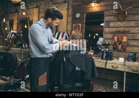 Male barber cutting hair of customer in barber shop - Stock Photo