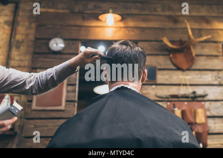 Male barber combing hair of customer in barber shop - Stock Photo