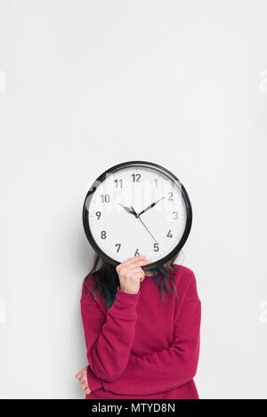 Woman holding clock over her face isolated on white - Stock Photo