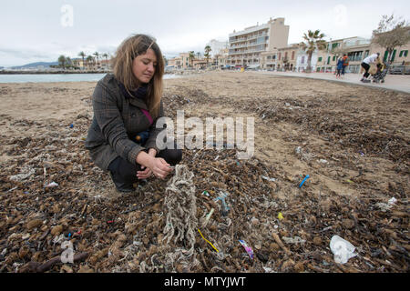 20 March 2018, Spain, Mallorca: Aina Barcelò from the environment organisation 'Ondine Baleares' examining rubbish on the beach in the Palma bay which has got mixed up with Neptune grass and sanitary products. Sewage works in Palma quickly become overburdened when it rains and raw sewage ends up flowing directly into the sea. The rubbish then lands on the beaches and mixes with the Neptune grass in the sand. Photo: Bodo Marks/dpa - Stock Photo
