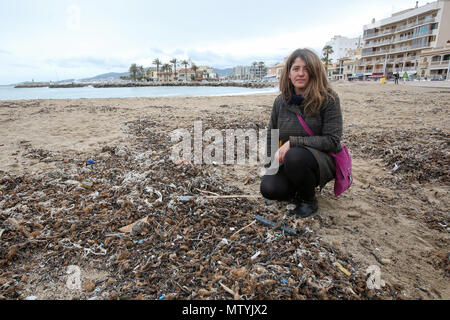 20 March 2018, Spain, Mallorca: Resident Aina Barcelò crouching on the beach where rubbish, mixed with sanitary products, is mixed with Neptune grass. Sewage works in Palma quickly become overburdened when it rains and raw sewage ends up flowing directly into the sea. The rubbish then lands on the beaches and mixes with the Neptune grass in the sand. Photo: Bodo Marks/dpa - Stock Photo