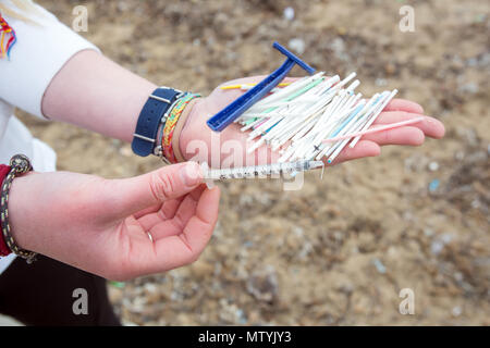 20 March 2018, Spain, Mallorca: Alice Mason from the environment organisation 'Ondine Baleares' showing remains from cotton buds, a syringe and a disposable razor that she found on the beach between other rubbish and sanitary products. Sewage works in Palma quickly become overburdened when it rains and raw sewage ends up flowing directly into the sea. The rubbish then lands on the beaches and mixes with the Neptune grass in the sand. Photo: Bodo Marks/dpa - Stock Photo