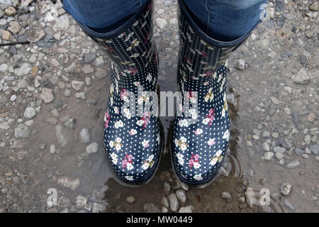 Woman wearing wellington boots standing in a puddle of water - Stock Photo