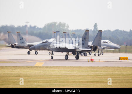 F-15C Eagles from the 48th Fighter Wing line up beside the runway at RAF Lakenheath to be dearmed after a training sortie. - Stock Photo