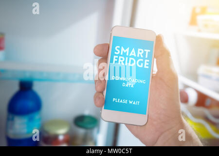 Internet of things, smartphone connecting with refrigerator to generate smart shopping list. Home kitchen appliance connecting with mobile phone and e - Stock Photo