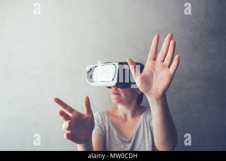 Woman immersed in virtual reality, female person using modern VR headset to experience 3d multimedia content - Stock Photo