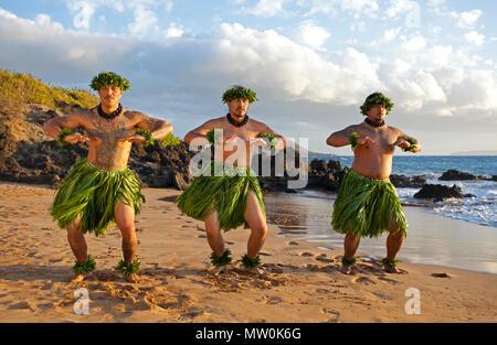 Three male hula dancers at Wailea, Maui, Hawaii - Stock Photo