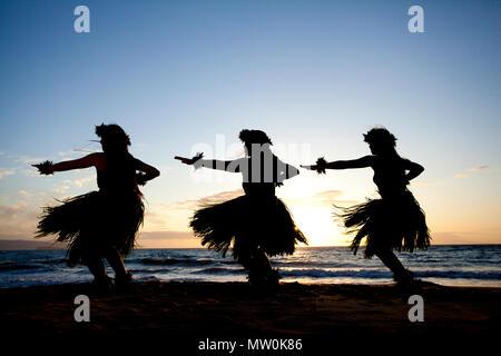 Three hula dancers at sunset at Wailea, Maui, Hawaii. - Stock Photo