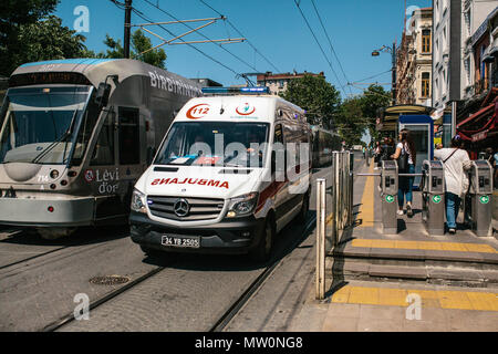 Editorial image of ambulance and urban over ground metro sitting next to each other in the middle of the day in Istanbul, Turkej on June 15, 2017. - Stock Photo