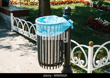 Close-up - iron trash urn with one-time package inside on the background of benches, fences and flowers in sunny park - Stock Photo