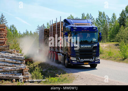Test drivers wave as they drive Next Generation Scania R730 logging truck on dusty road during Scania Tour 2018 in Lohja, Finland - May 25, 2018. - Stock Photo