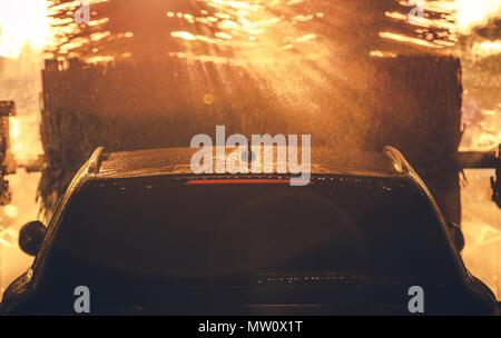 Car Washing in the Sun. Sun Rays Between Car Wash Brushes. Transportation Industry Theme. - Stock Photo