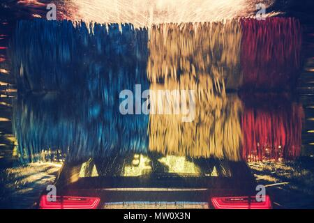 Colorful Car Wash in Action. Modern Vehicle Inside the Spinning Washing Brushes. - Stock Photo