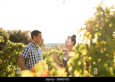 Dark haired woman talking to a man outside in nature with him wearing a blue and white checkered shirt - Stock Photo