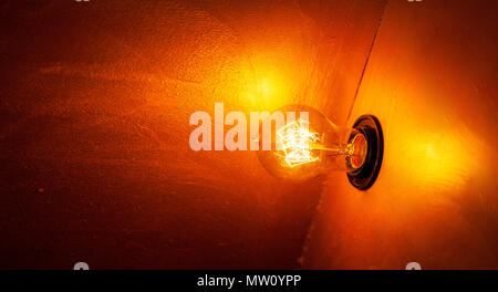 Glowing orange light bulb in the dark with copy space - Stock Photo