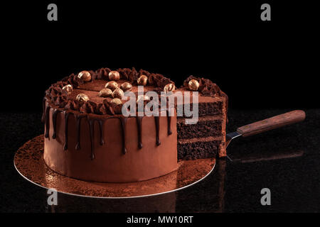 Chocolate cake with nuts on a black background - Stock Photo