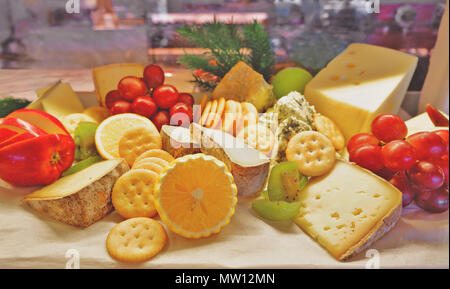 Choices of cheese variety with fruits and biscuits on a board at a lunch buffet restaurants - Stock Photo