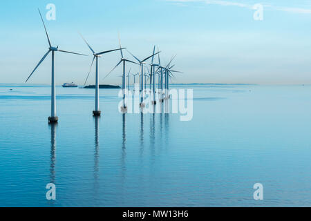 windmill farm in the sea with reflection morning - Stock Photo