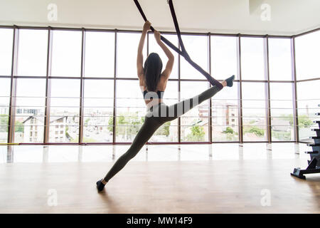Sport healthy lifestyle concept. Copy space. Fit pretty young woman wearing sportwear doing fly yoga stretching exercises in fitness training white gy - Stock Photo