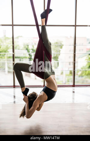Fit young woman doing fly yoga stretching exercises in fitness training at gym hall . Sport and healthy lifestyle concept. - Stock Photo