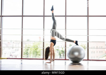 Young slim Woman in sportswear exercising her abs on a Pilates ball of fitball close up at gym. - Stock Photo
