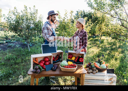 two smiling gardeners shaking hands while standing near stall at farmers market - Stock Photo