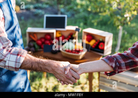 cropped shot of two gardeners shaking hands at farmers market - Stock Photo