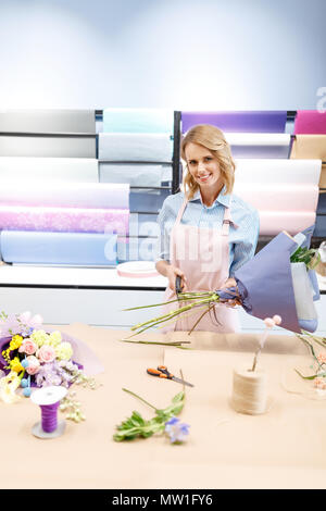 beautiful smiling florist in apron cutting stems and arranging bouquet in flower shop - Stock Photo