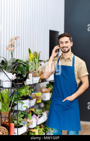 handsome smiling male florist talking on smartphone while working in flower shop - Stock Photo