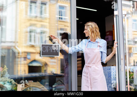 smiling young florist in aorn holding open sign while standing in doorway of flower shop - Stock Photo