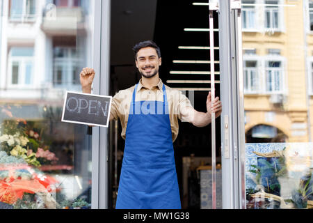 happy young florist in apron holding open sign and smiling at camera - Stock Photo