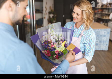 cropped shot of man paying with credit card for a bouquet and smiling florist in flower shop - Stock Photo