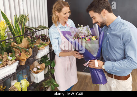 smiling female florist looking at bearded young client smelling flowers in flower shop - Stock Photo
