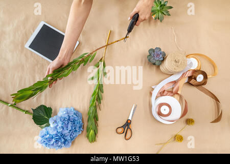 cropped shot of female florist with secateurs cutting stem while arranging plants - Stock Photo