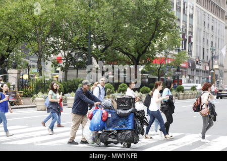 Homeless man pushes a cart full of belongoings and soda cans across 6th Avenue on 34th Street in Manhattan. - Stock Photo