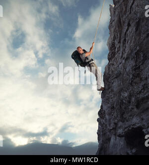Man climbs a high danger mountain with a rope - Stock Photo