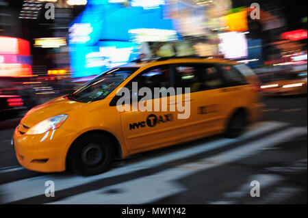 New York taxi van moving through Times Square with blur of lights beyond, New York, NY, USA - Stock Photo