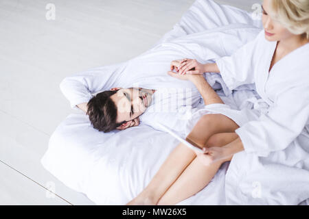 young couple in bathrobes holding hands while girl using digital tablet on bed - Stock Photo