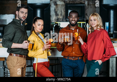 group of happy friends with with various alcohol beverages spending time together in bar - Stock Photo