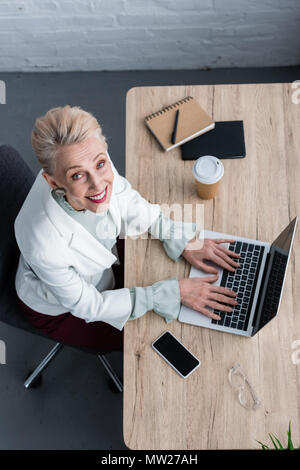 overhead view of smiling senior businesswoman using laptop at workplace - Stock Photo