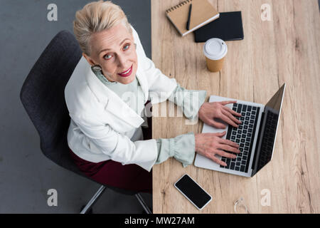 overhead view of elegant business woman working with laptop in modern office - Stock Photo