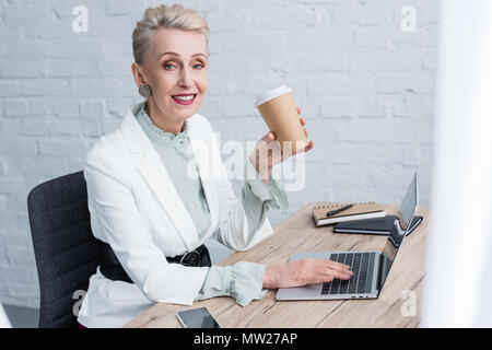 smiling senior businesswoman with disposable cup of coffee using laptop in office - Stock Photo