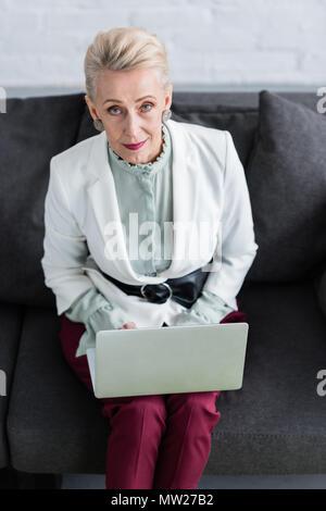 overhead view of beautiful senior business woman using laptop on sofa - Stock Photo