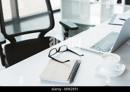 close-up view of eyeglasses, notebook, cup of coffee and laptop on table in office - Stock Photo