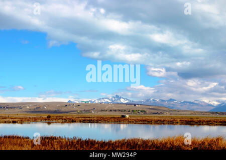 A range of clouds gather above the Laguna Nimez in El Calafate, southern Argentina and above the mountains in the background. - Stock Photo